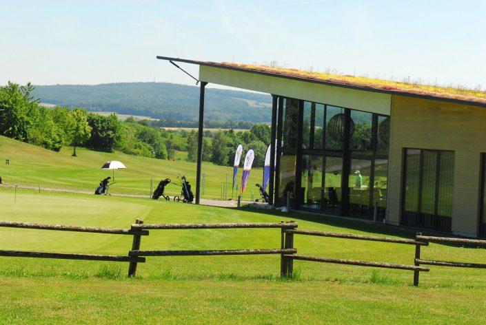 Blick über das Putting Green zum Golfclub Praforst Clubhaus